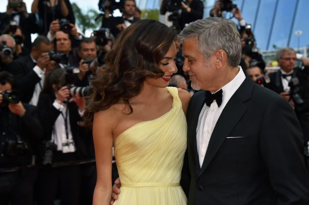 """US actor George Clooney (R), and his wife British-Lebanese lawyer Amal Clooney pose on May 12, 2016 as they arrive for the screening of the film """"Money Monster"""" at the 69th Cannes Film Festival in Cannes, southern France. / AFP PHOTO / LOIC VENANCE"""